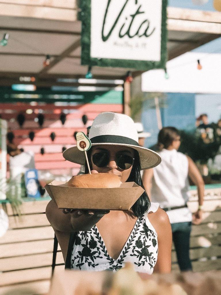 girl holding a vegan burger in a festival